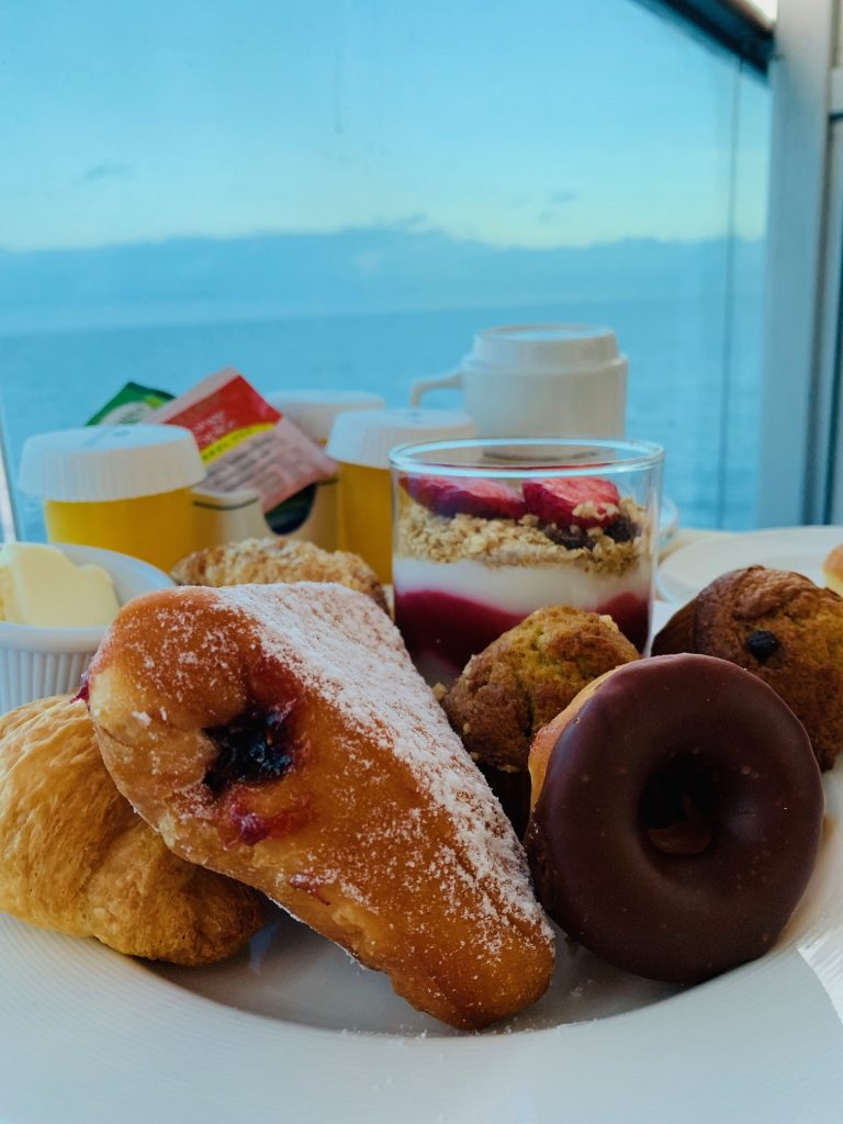 plate of breakfast pastries and parfait with ocean in background