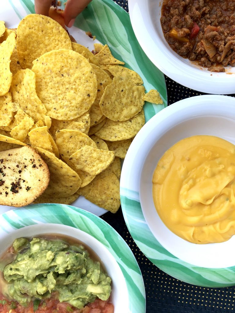 overhead photo of tortilla chips with queso dip, salsa, and guacamole