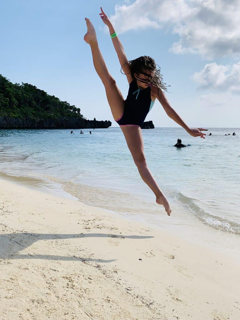 photo of teenage girl doing a vertical split leap on the beach