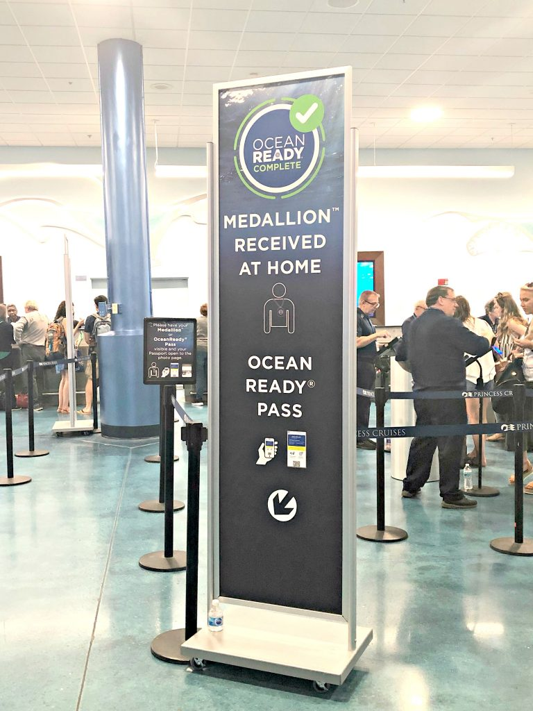 photo of a sign pointing to a queue. sign reads: Ocean Ready Complete. Medallion recieved at home. Ocean Ready pass