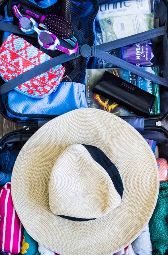 photo of packed suitcase for a cruise. sun hat, goggles, hair brush, toiletries, clothes