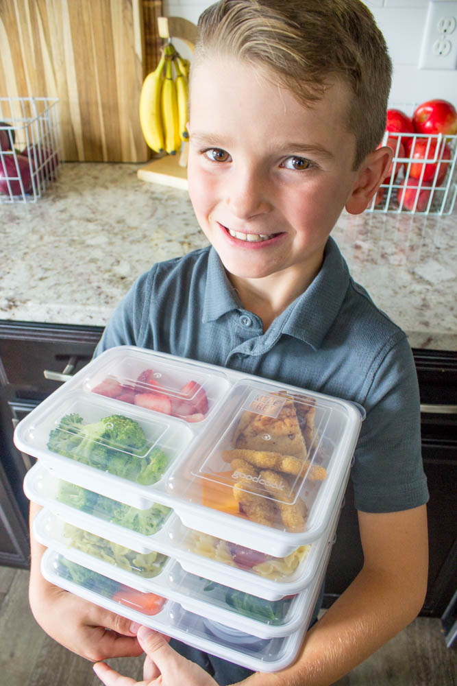 photo of a boy holding prepped lunch boxes
