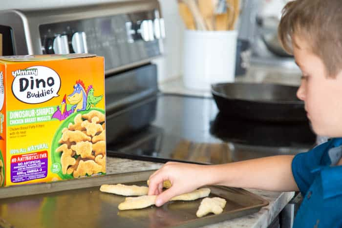photo of a boy putting dino buddies nuggets on a sheet pan
