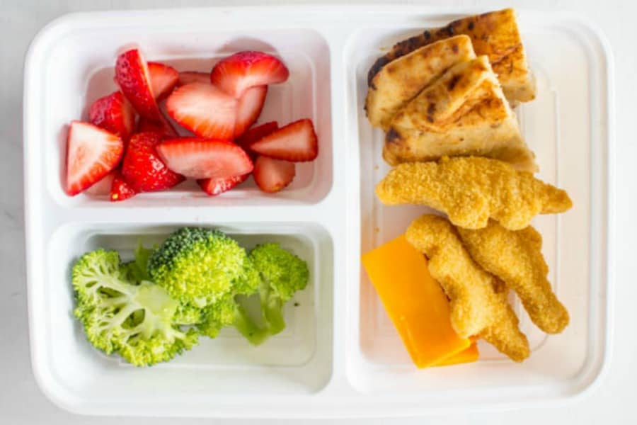 photo of lunch box with strawberries, broccoli, pita bread triangles, chicken nuggets, and cheese slices