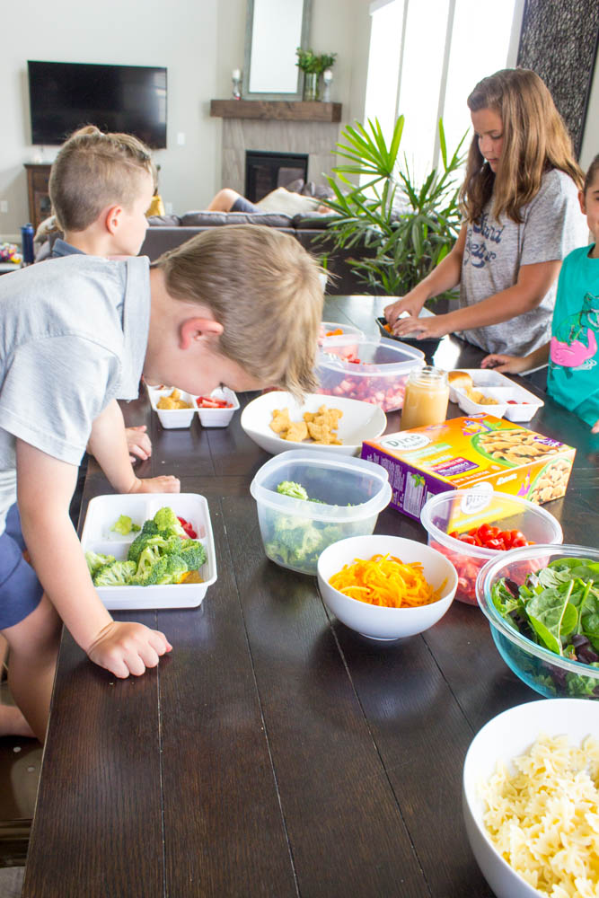 photo of kids sitting around table with bowls of prepped food, putting together their lunch boxes