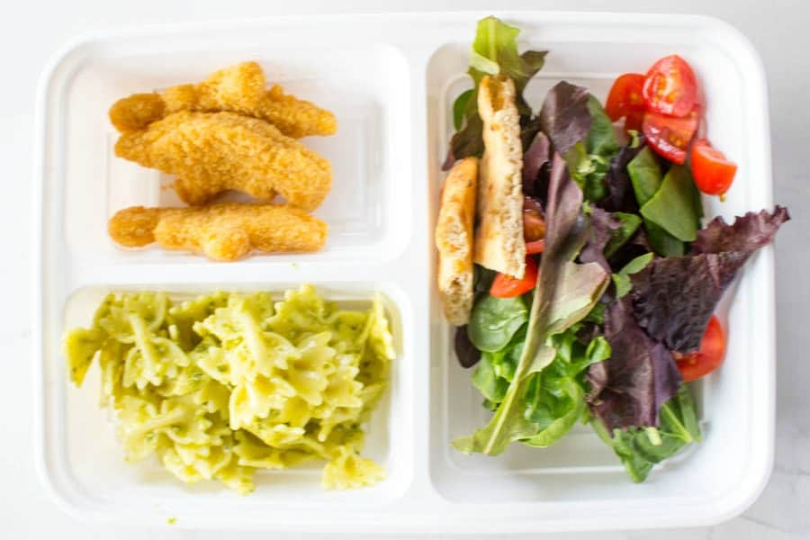 photo of lunch box with nuggets, bowtie pasta with pesto, and mixed salad greens with pita and tomato pieces
