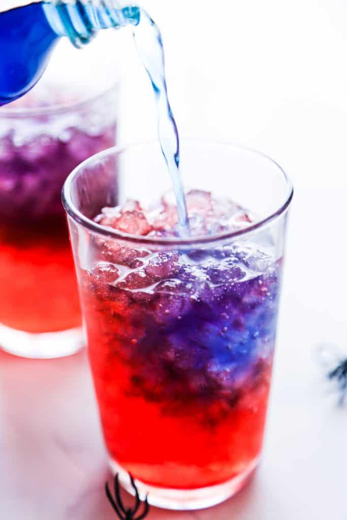 Blue gatorade being poured into a cup with red soda and ice