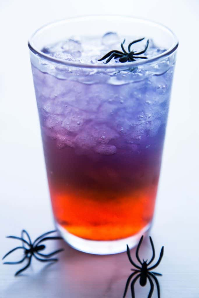 photo of a glass of spiderman punch with spider rings in and around glass