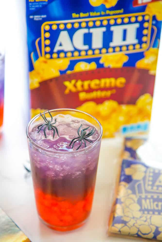 photo of glass of punch with popcorn box in the background