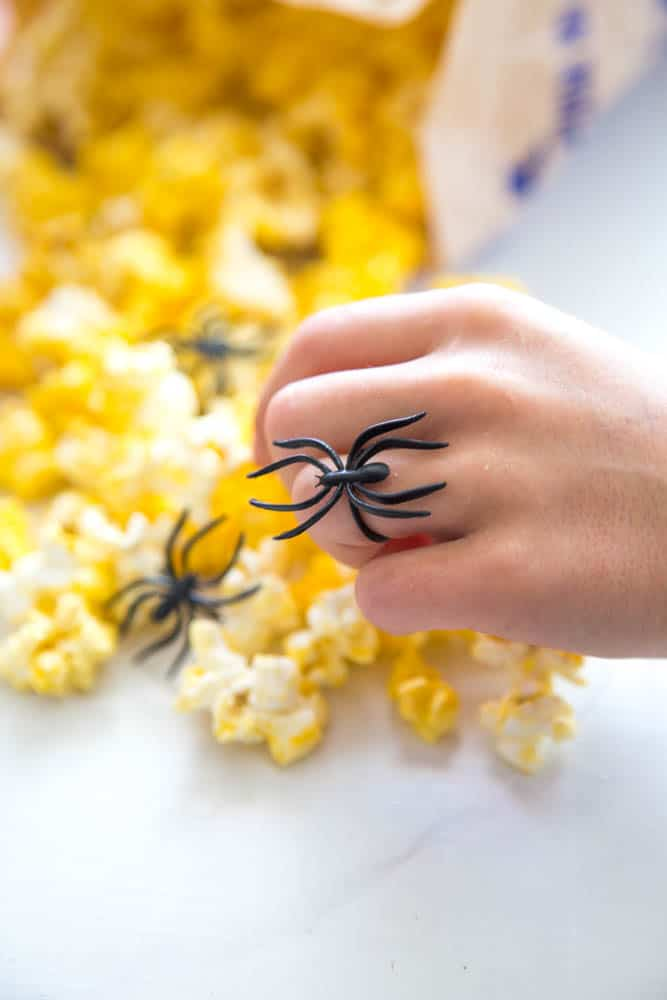 photo of a hand wearing a black spider ring grabbing popcorn from the bag