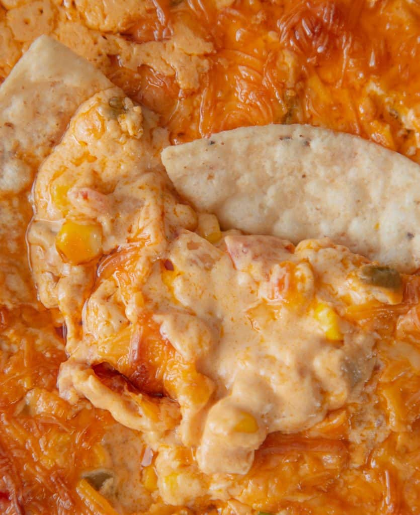 close up of corn queso dip with tortilla chips