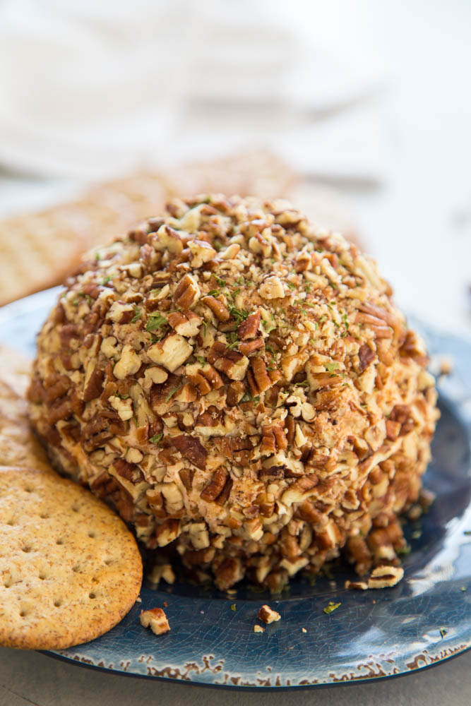 photo of classic cheeseball on a blue plate with ritz crackers on plate