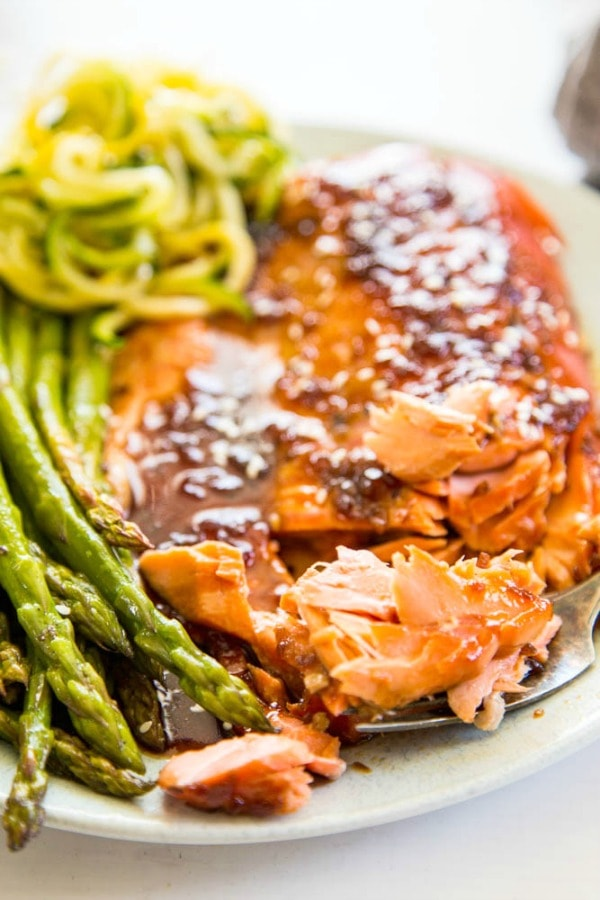 grilled salmon with a side of asparagus and zucchini noodles, salmon has a teriyaki glaze on it