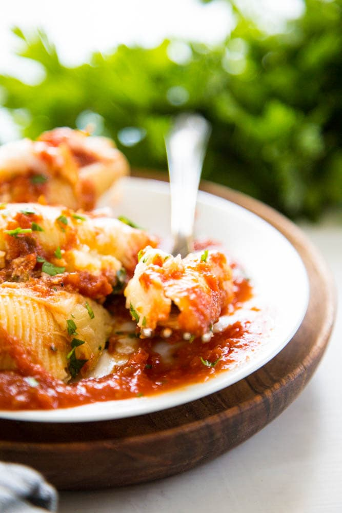 photo of stuffed shells and sauce on a plate with a fork.