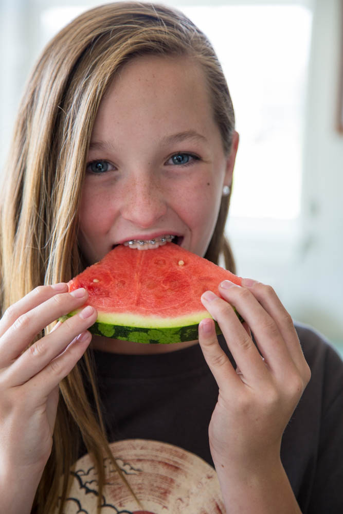 photo of a girl eating a slice of watermelon