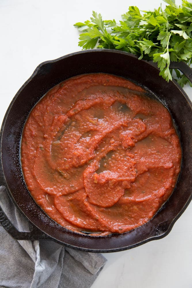 a cast iron skillet coated in marinara sauce.
