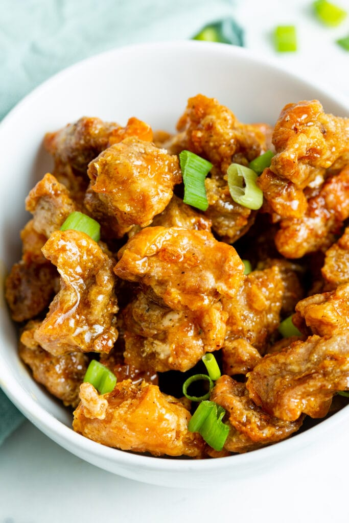 crispy honey chicken garnished with sliced green onions.