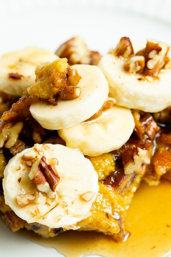 slice of french toast with bananas, nuts and syrup.