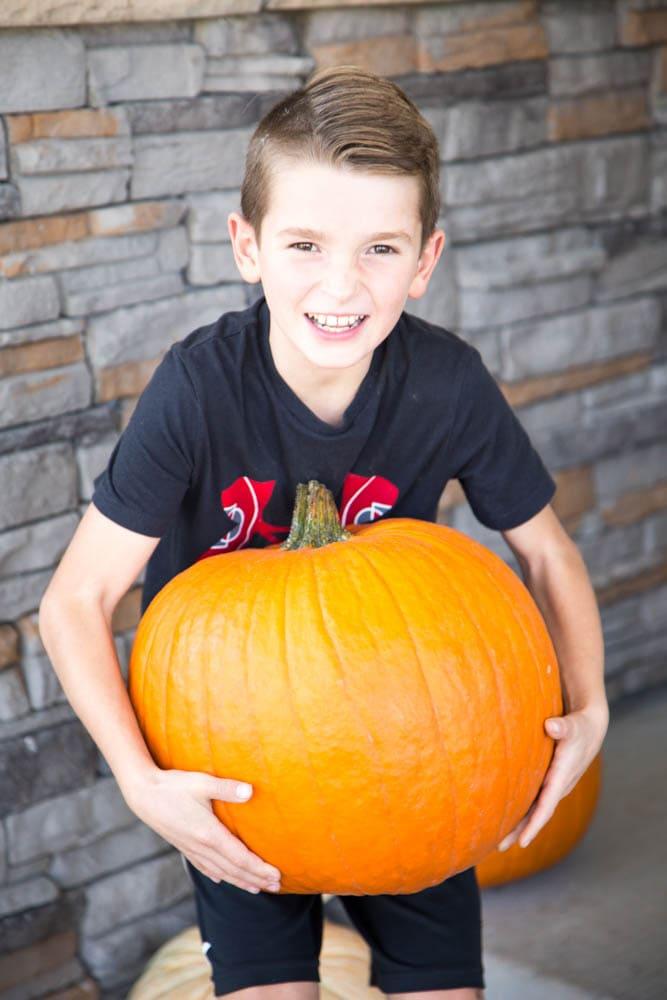 a boy holding a large pumpkin.