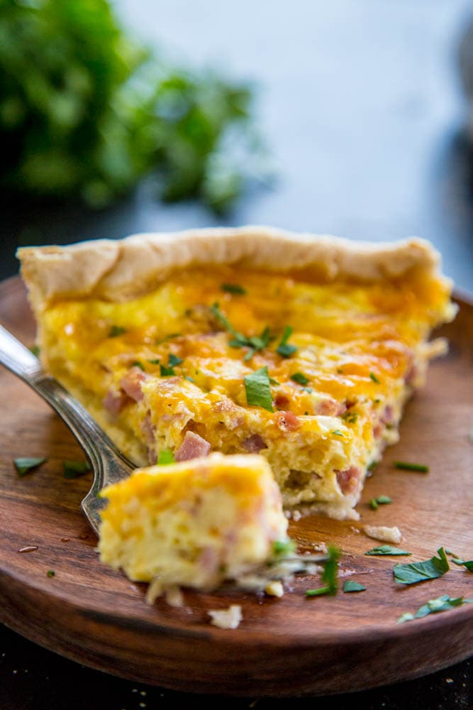 a fork with a bite of quiche with the rest of the slice