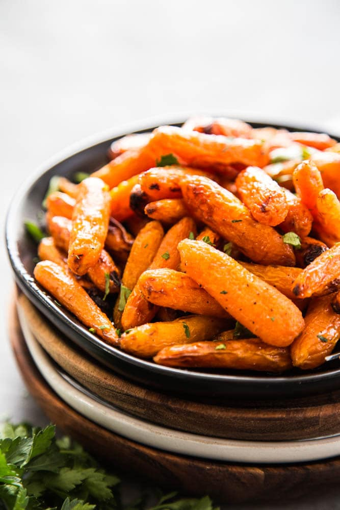 air fryer carrots on a stack of plate with fresh parsley