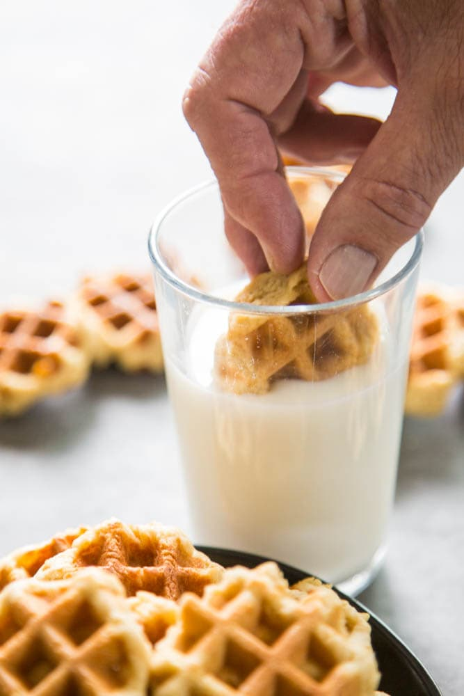 a cookie being dunked in a glass of milk