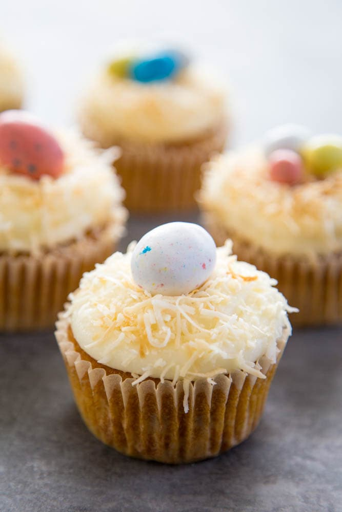 carrot cake cupcakes topped with frosting, coconut, and a candy egg.