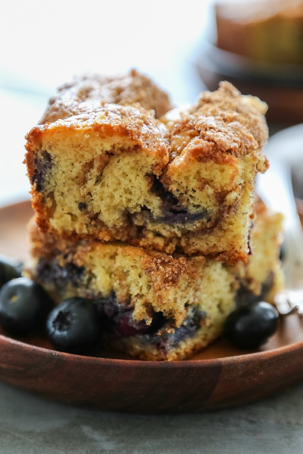Two slices of coffee cake stacked on a plate with blueberries.