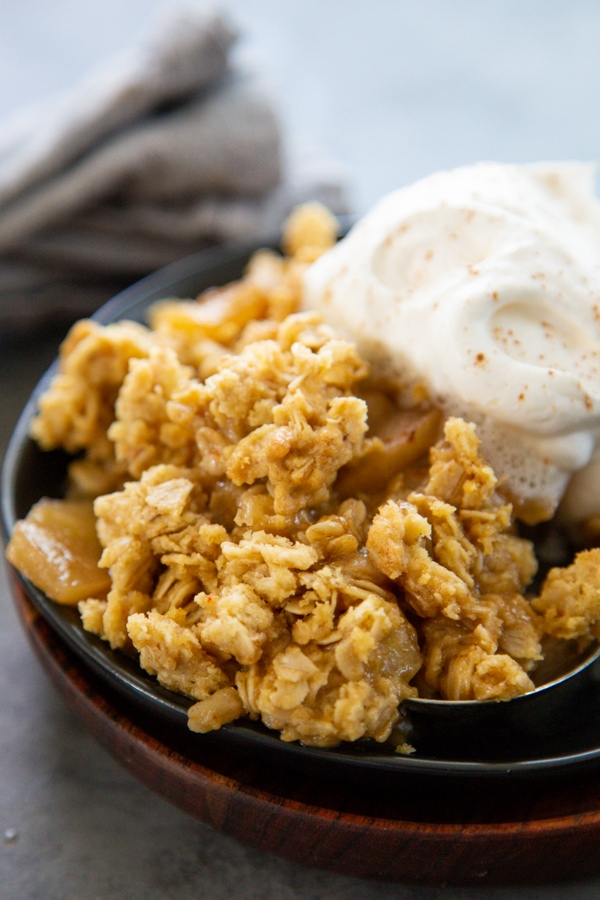 close-up shot of an apple crisp on  a plate with whipped cream.
