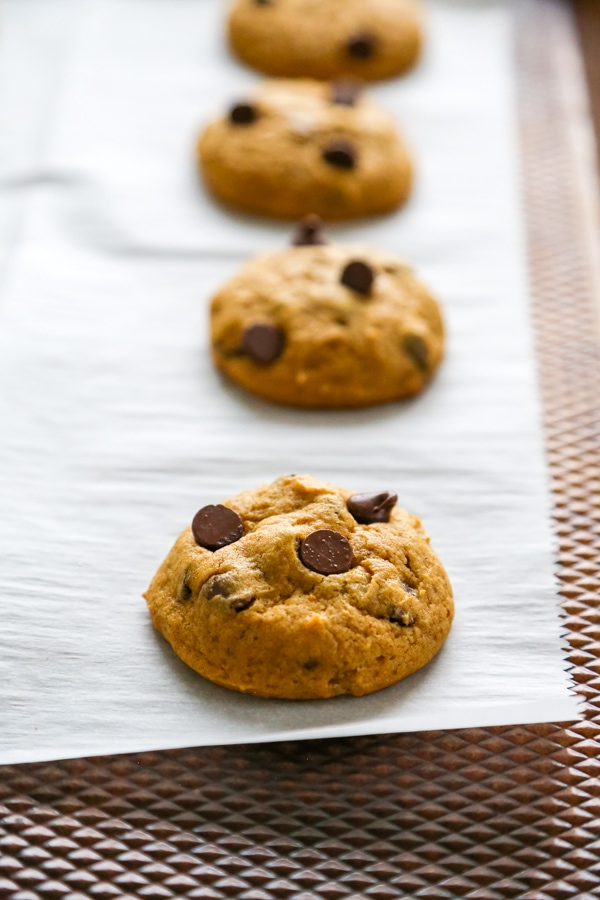 baked cookies lined up on the parchment paper.