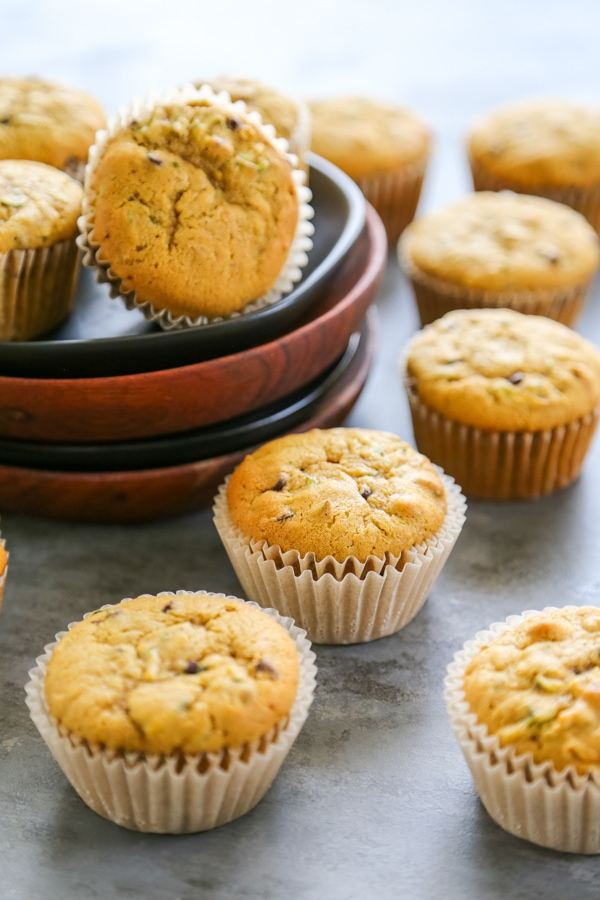 muffins lined up on a table and also on a plate.