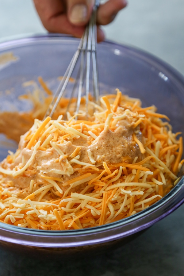 the chicken enchilada filling being mixed in a bowl.