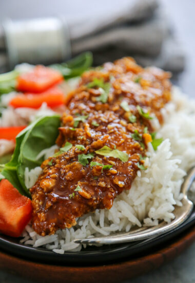 cashew crusted chicken on a plate with rice.