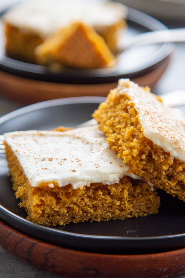 two frosted pumpkin bars on a plate.
