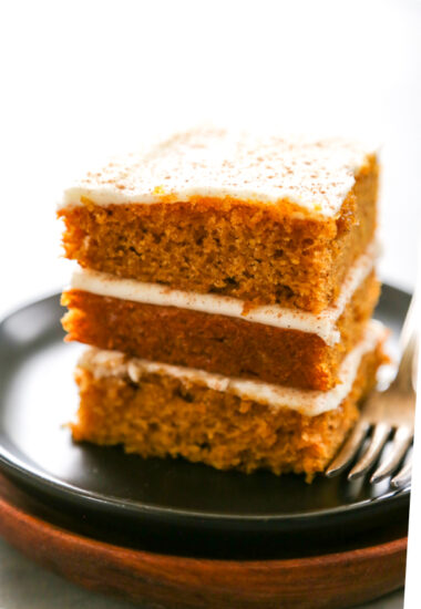 three stacked pumpkin bars with cream cheese frosting.