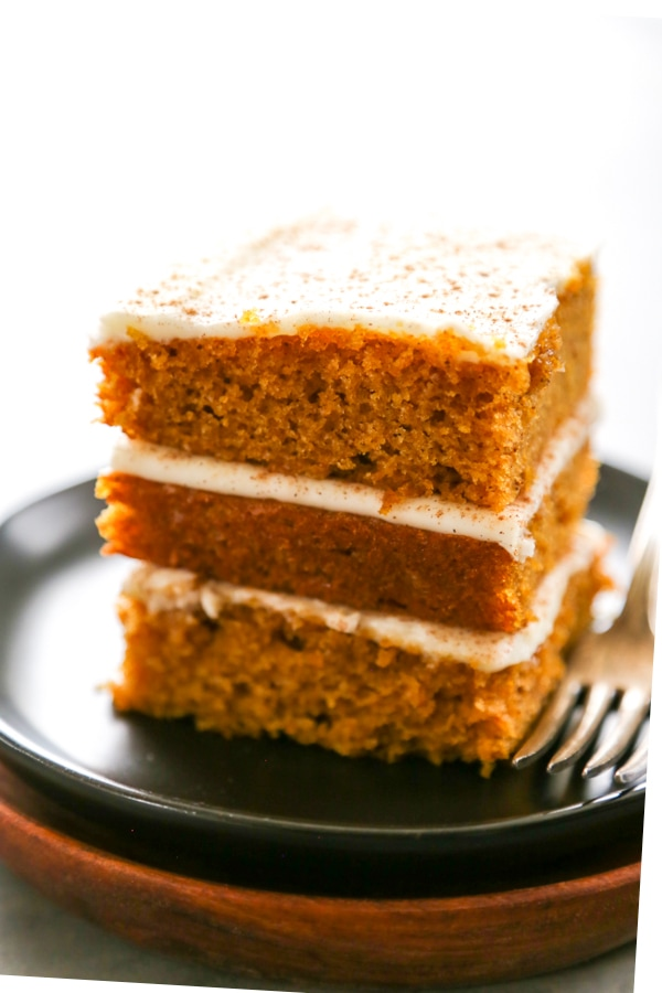 three pumpkin bars stacked on a plate.