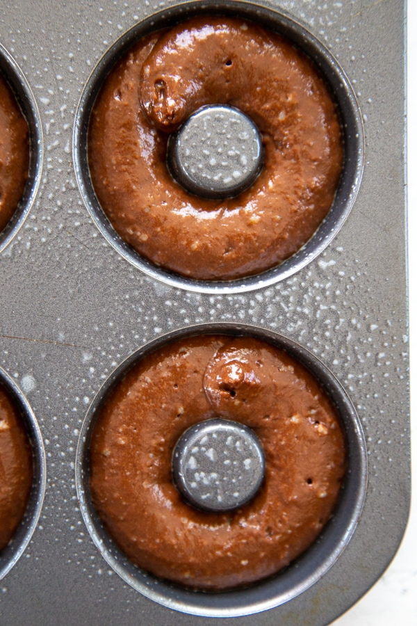 the batter piped into the donut pan.