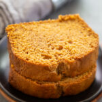 two pieces of pumpkin bread stacked on a plate.