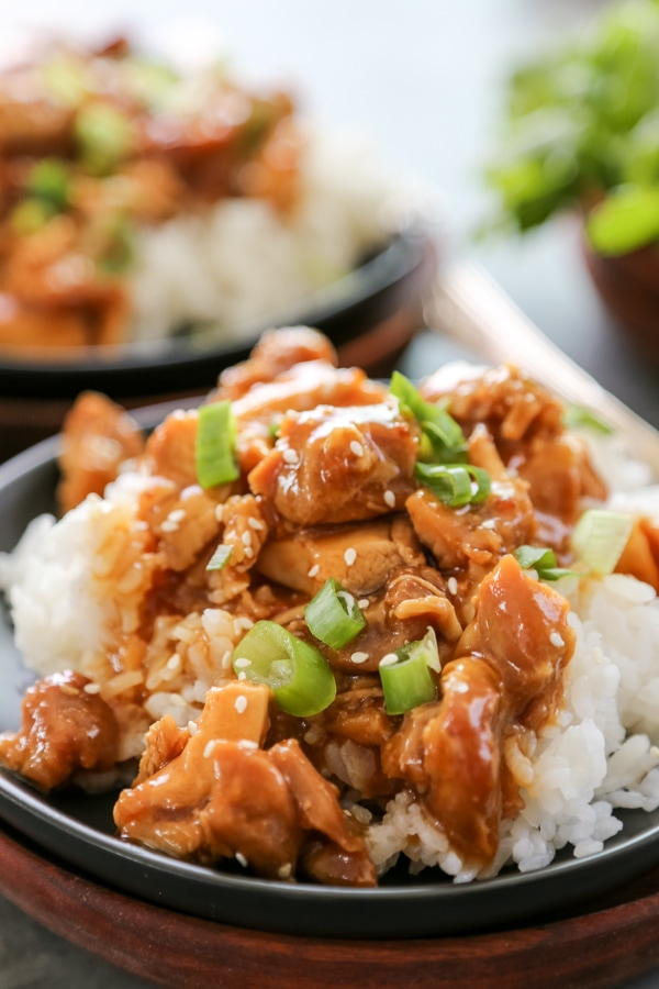 a plate of orange chicken with rice.